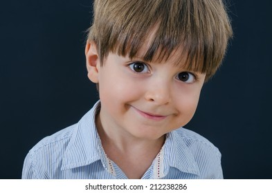 Smart little boy in a striped shirt on black background