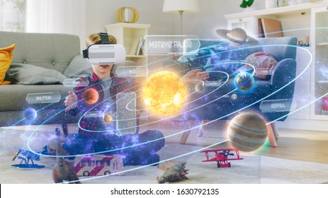 Smart Little Boy Wearing Virtual Reality Headset and Looking at Our Digitally Generated Solar System with Sun and Planets. Space Exploration with AR Glasses. He's Sitting on Carpet in His Living Room.