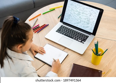Smart little Caucasian girl child sit at table study at laptop make notes write in notebook, small schoolgirl handwrite prepare homework assignment at home, distant education concept