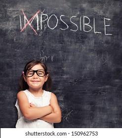 smart little girl smiling in front of a blackboard