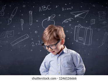 Smart little kid in front of a drawn up blackboard ruminate