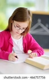 Smart little schoolgirl with pen and books writing a test in a classroom. Child in an elementary school. Education and learning for kids.