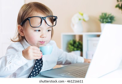 Smart little toddler girl with big glasses drinking coffee while using her laptop