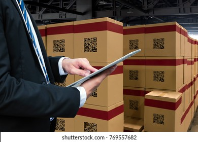 Smart logistic industry 4.0 , QR Codes Asset warehouse and inventory management supply chain technology concept. Businessman using tablet and group of boxes in storehouse can check product inside.