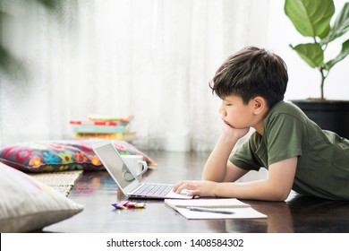 Smart looking Asian preteen boy using laptop computer in his room, lying on wooden floor, putting hands on cheek, staring at computer screen as he is tired, stressed, frustrated doing homework.