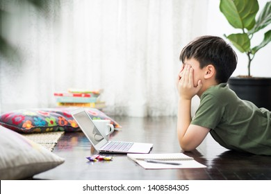 Smart looking Asian preteen boy using laptop computer in his room, lying on wooden floor, covering his face with his hands as he is stressed, frustrated doing homework and preparing for examination.
