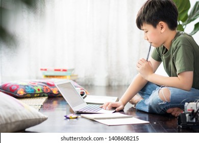 Smart looking Asian preteen boy sit crossed legs, holding pen against his lips, thinking and looking at computer laptop at home due to Covid-19 pandemic and social distancing measures