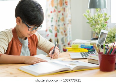 Smart looking Asian teen boy wear glasses, write homework, take notes from online lessons, preparing for the exam due to pandemic of Covid-19 and social distancing. Online Learning Technology. Preteen