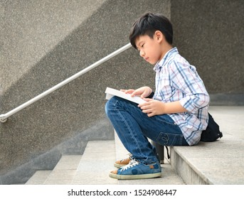 A smart looking asian tween / teen student boy sitting on the stairs in front of a library or collage campus concentrate on reading textbook preparing for his exams. Teenager self esteem concept.