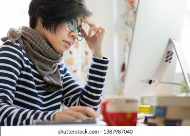 Smart looking Asian woman worn out. Blue Blocking Glasses preventing blue light from LED computer screen which can cause sleeping problem and digital eye strain. Computer Vision Syndrome (CVS) concept