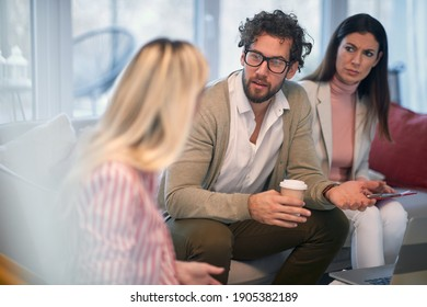 A smart looking businessman having a meeting in a working atmosphere with his female colleagues. People, business, meeting