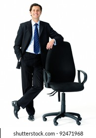 Smart looking businessman leans on an empty office chair to indicate an open position, suitable for recruitment campaigns