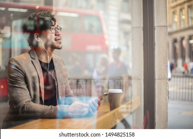 Smart looking man sitting in a cafe, listening to something on his phone