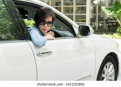 Smart looking middle aged Asian woman is driving a car backward to park in parking lot of nice restaurant slowly and carefully. Driving lessons and training.