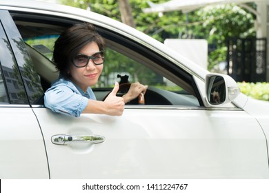 Smart looking middle aged Asian woman lean her arm out of car window and thumbs up while driving a car backward to park in parking lot of nice restaurant slowly and carefully. Driving lessons and trai
