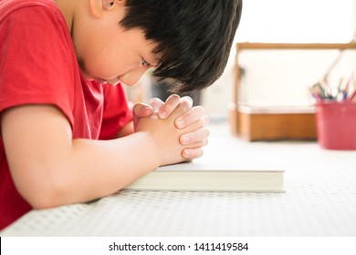 Smart looking preteen Asian boy desp praying to God with eyes opened, joined hands over hard cover bible.