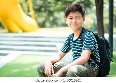 A smart looking preteen student boy siting outdoor under the tree shade in front of the school. Back to school, Preteen, Tween, Education, Friendly, Healthy, Growing up concept.
