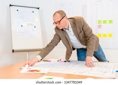 Smart male architect reaching for document while working on blueprint in office