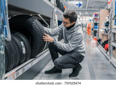 Smart male customer choosing new tires in the supermarket for buying. Big shopping mall with car goods.