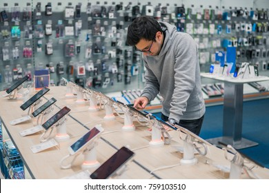 Smart male customer choosing smartphone in the mobile phone shop. difficult decision. Various choice. He is smiling