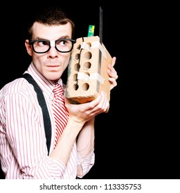 Smart Male Nerd Inventor Holding A State Of The Art House Brick Transformed Into A Mobile Phone In A Novelty Concept Of Innovation
