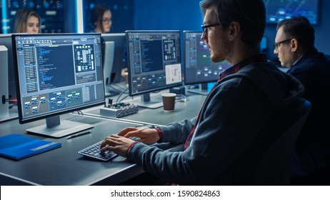Smart Male IT Programer Working on Desktop Green Mock-up Screen Computer in Data Center System Control Room. Team of Young Professionals Programming Sophisticated Code