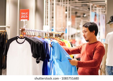 Smart man with beard choosing clothes in clothing store at shopping center, looking t-shirts sale 20% off, Fashion and Consumerism Concept.