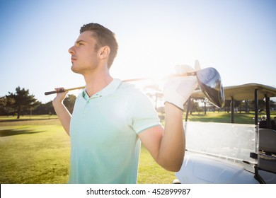 Smart man carrying golf club while standing on field