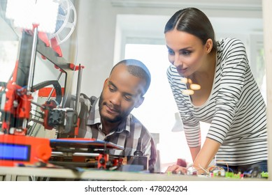 Smart man and woman watching 3d printing