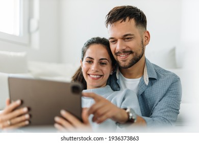 Smart man and woman, watching something together, over the digital tablet.