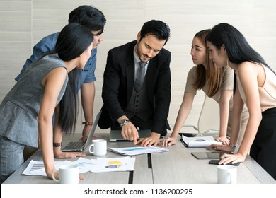 Smart manager explaining internal meeting to his project team in modern office. The multi ethnic business person group in suit. Project and Business concept.