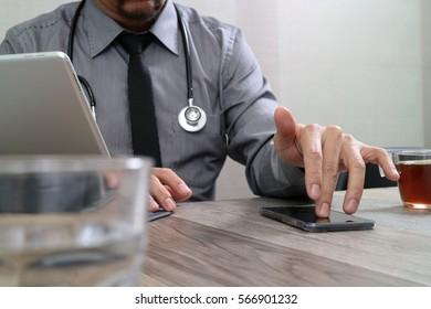 smart medical doctor hand working with smart phone,digital tablet computer,stethoscope eyeglass,on wood desk