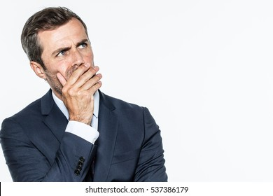 smart middle aged businessman thinking, looking up with hand hiding his mouth, expressing leadership reflections and concerns, copy space, white background studio