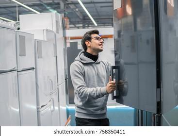 Smart modern male customer choosing large fridges in domestic appliances section. He looks happy