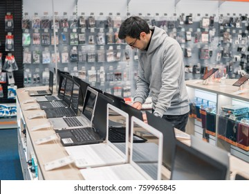 Smart modern male customer choosing laptop in the computer store. difficult decision