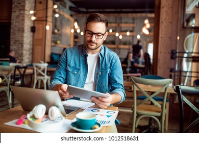 Smart modern young man working remotely from cafe