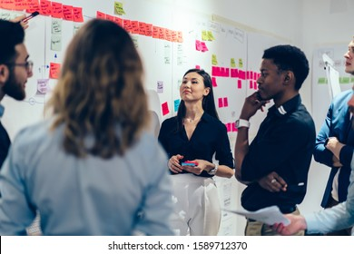 Smart multiethnic male and female coworkers in formal clothing setting goals with colorful sticky notes and discussing at creative office