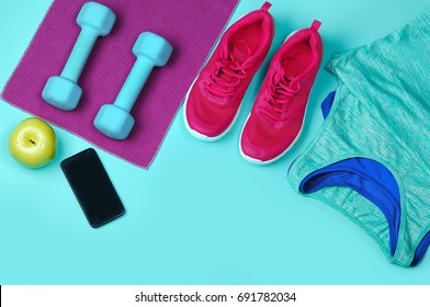Smart phone, apple and set of fitness clothes on teal background