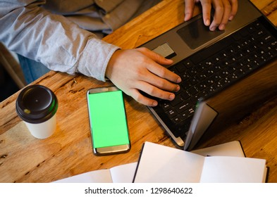 smart phone with blank green screen against man using laptop