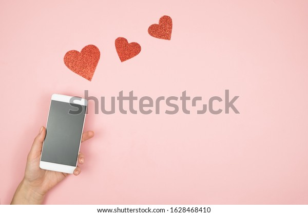 Smart phone with blank screen in hand and hearts on old wooden table