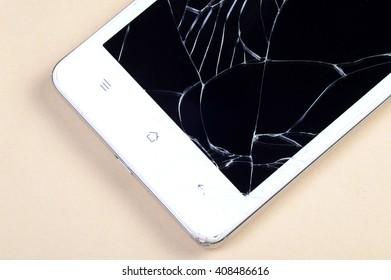 Smart Phone with broken screen on cream background