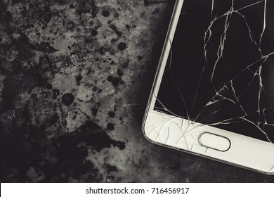 Smart phone with broken screen on dark background. Close-up.