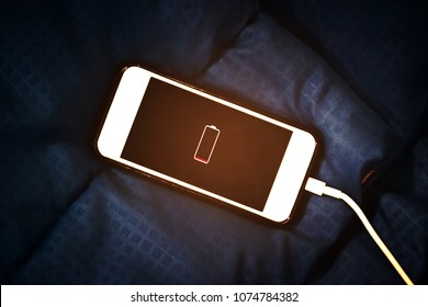 Smart phone is charging on the bed and lying on blue fabric background - Smart phone addict and Healthy lifestyle concept. Low battery and need to charge or rest. (Abstract blurred - Soft focus)