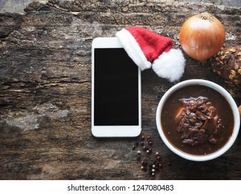 Smart phone with christmas hat and onion soup