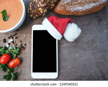 Smart phone with christmas hat and soup on table food