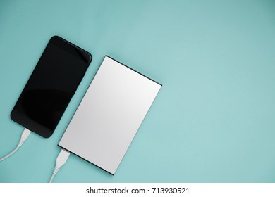 Smart phone connect to power bank on top view.