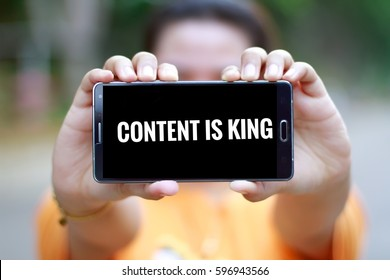 Smart phone display text 'CONTENT IS KING'.