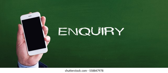 Smart phone in hand front of blackboard and written ENQUIRY