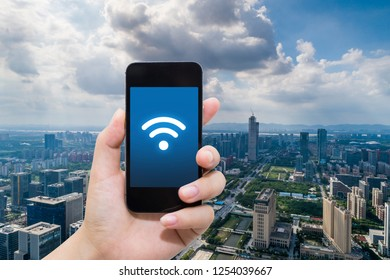 smart phone in hand and using internet wifi network connection communication technology on city background