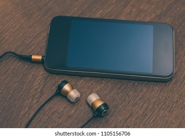 Smart phone with headphones lay on wooden table